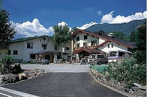スイス風の外観の宿。背景に乗鞍岳を望む