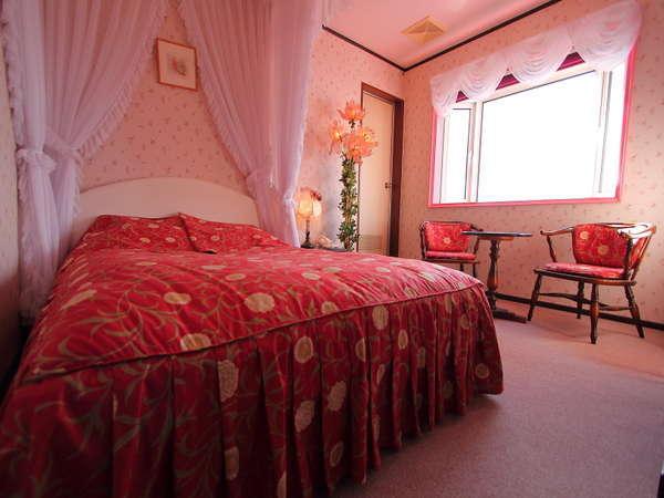 大きな出窓とベッドを囲む白のレースカーテンと花柄の赤が鮮やかなフリルのバッドカバーで優雅さを演出。