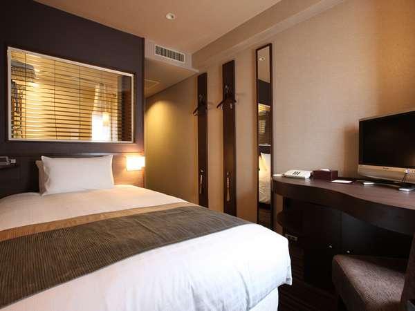シングルルーム(禁煙&喫煙)ゆったりしたベッド。バスルームとはガラスで仕切られ、開放感を演出。
