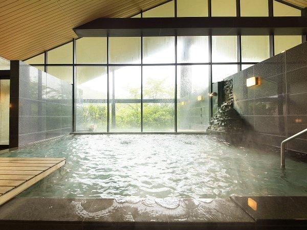 せせらぎの湯処:大きな三角窓で採光をたっぷりと取り入れた明るい男性用大浴場。