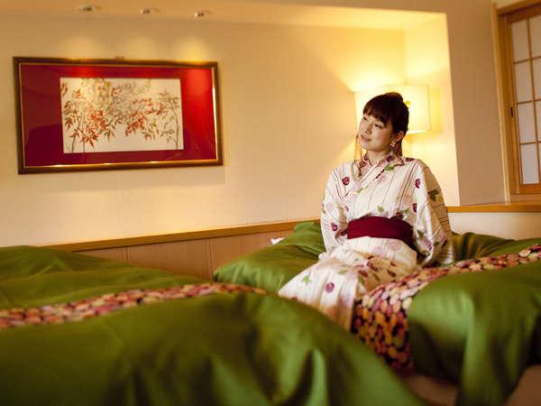 【露天風呂付特別和洋室】大きな陶器露天がある部屋のフカフカのツインベッドはシックな若草色で統一。