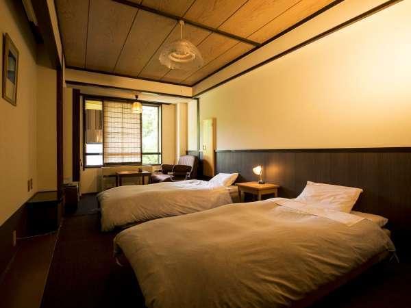 【スタンダード洋室21㎡・定員3名】カーペットの上にベッドがあり、靴を脱いでゆったり過ごせる