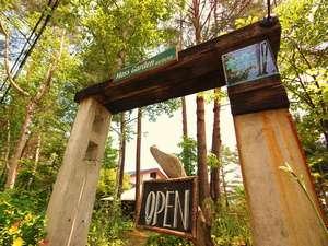 枕木とコンクリートの「門柱」、隠れ家的な小さいガラス製のロゴマーク、当館への入り口です