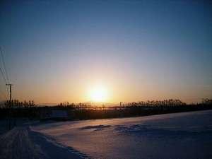 """村から望む""""オホーツク海に連なる知床の山並みから昇る 日の出 """""""