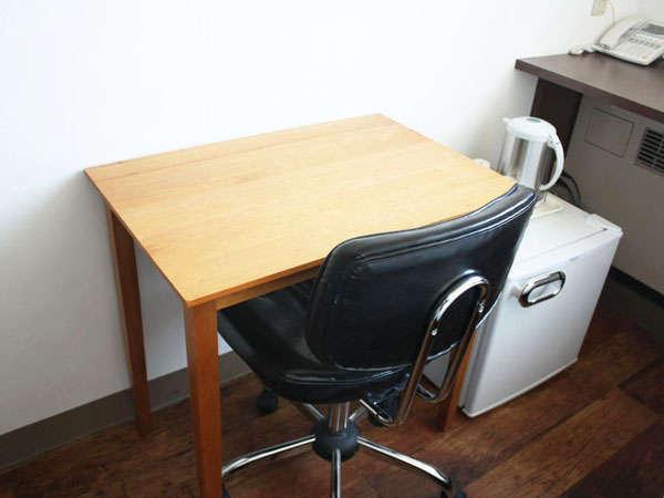 シングルルームのテーブルとイス、冷蔵庫の写真です。