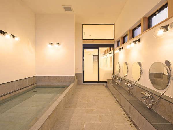 高さのある天井と大きな窓、広い浴槽が自慢の大浴場【めぐみの湯】。奥には半露天の壺湯も!
