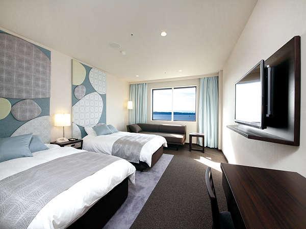 ラグジュアリーツインのベッドはシモンズ製のデュベスタイル。TVは壁掛けタイプ。