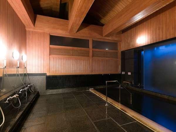 檜の香りと黒御影石を敷き詰めた大浴場。