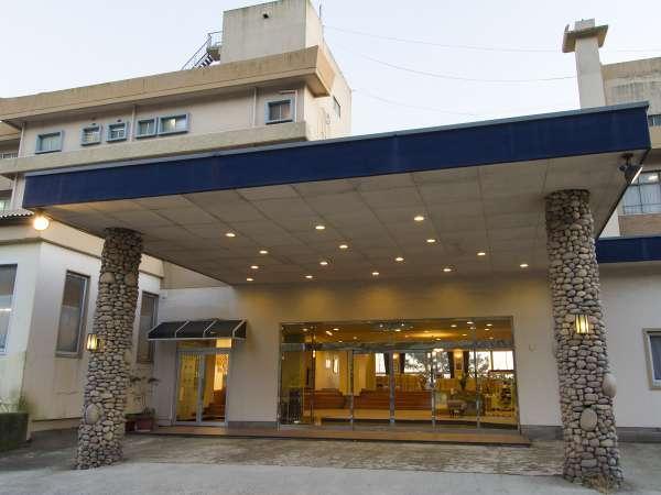 玄関|小石を積上げた特徴的な2本の柱がお出迎え。駐車場は、玄関右側のスペースにお止め頂けます。