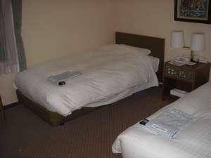 白を基調としたツインルーム。清潔感あふれるベッドでぐっすり♪