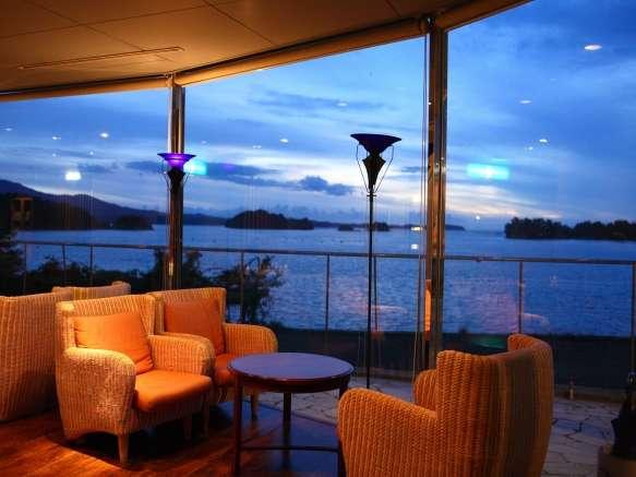 コーヒーラウンジから夕暮れの海を眺める