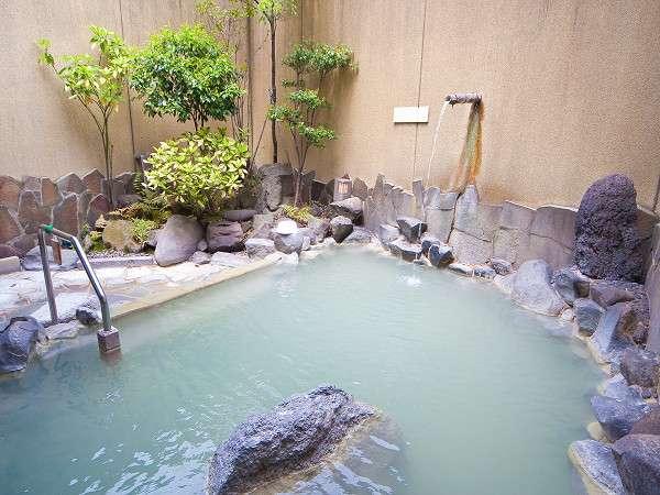 源泉掛け流しの大浴場露天風呂。白濁の温泉は体をやさしく包んでくれます。