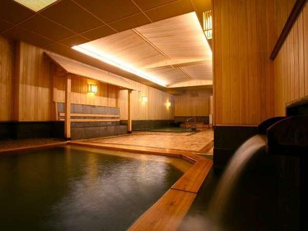 香り高い檜と軟石を使用した大浴場。大小の湯船を備えております。