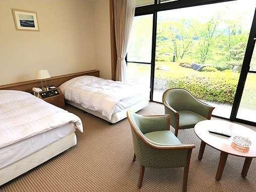 ホテル棟ツインルーム。大きな窓からは自然を一望できる。ゆったりした時間をお過ごしください。