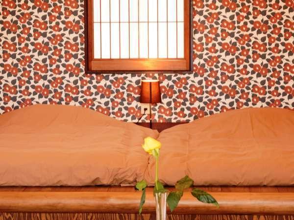露天風呂付き客室「つばき」枕もとの壁紙は、部屋名称の由来である竹下夢二の「つばき」を配した。