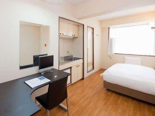 広めの部屋(約8畳)にセミダブルのベッドと大きな机を備えています。