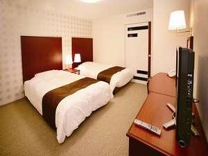 デラックスツイン例。デュベタイプのふわふわベッドも多数。照明にシーリングライトを使用し、明るい客室