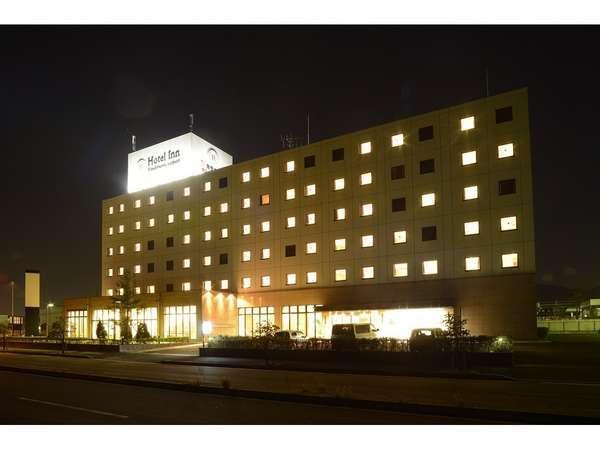 ホテル外観(夜)白のネオンサインが遠くからでもはっきりと浮かんでいます。