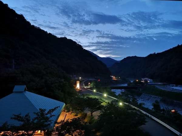 夏の宵、客室の窓からの眺め。渓谷に夕闇がにじむように広がっていきます。