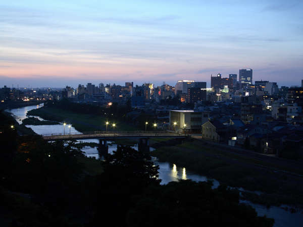 全室上層階のジュニアスイートから望む金沢市街と犀川の夕景。