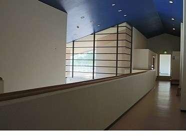二階の廊下壁面がガラス張り、天井の青が天空?のよう