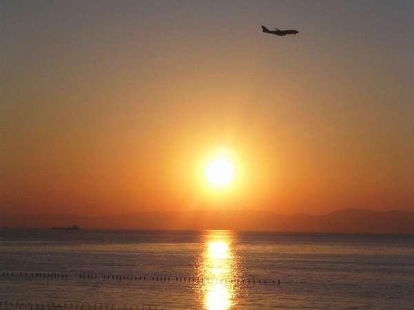 当宿横の海岸から撮影した夕日と飛行機