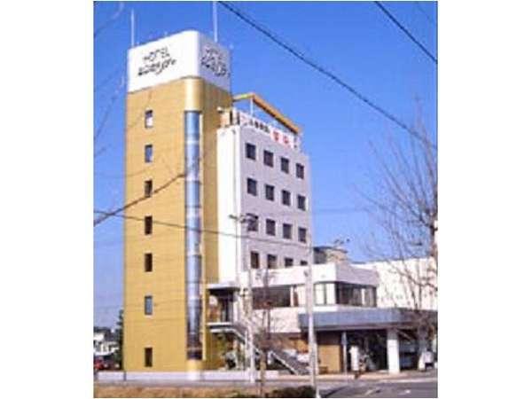 7階建ての黄土色と白の建物です。屋上に看板が見えます。