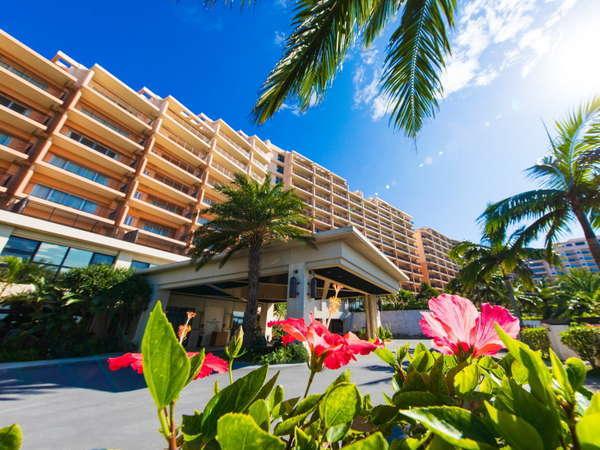 南国の青い空と緑に包まれるホテル外観 正面には海が広がります