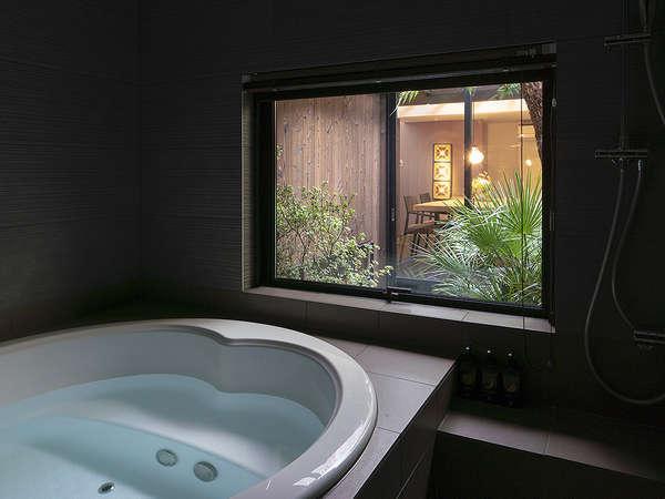 中庭の景色が望める浴室。浴槽に照明付きジャグジーが備わり、優雅な時間が旅の疲れを癒してくれます。