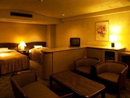 和洋室(和室8畳+ツインベッド) テーブルでの食事も可能です。