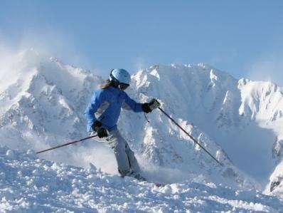 八方を滑るスキーヤー、後方は白馬槍ヶ岳