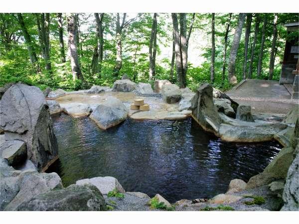 雨飾荘から徒歩2分、森の中の露天風呂は野趣あふれる岩造りのお風呂。