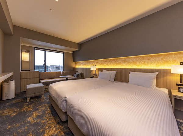 デラックスツイン(洗い場付きバス)ソファベッドを使用し3名利用も可能。広めの空間とバスが快適な客室。