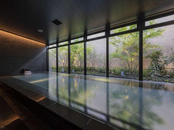 自然を感じる庭を望みながら一日の疲れを癒せる湯どころ(大浴場)