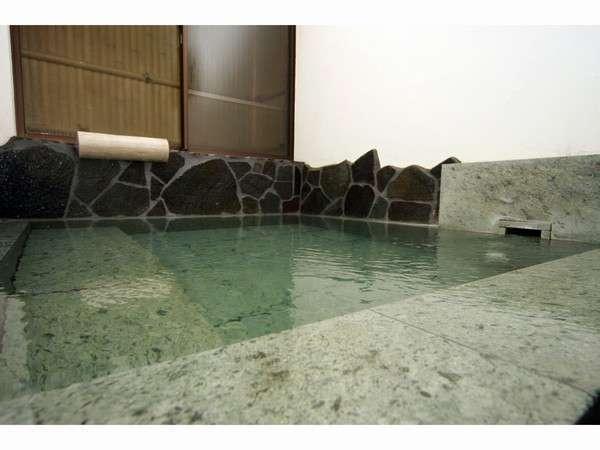 グリーンの色が綺麗な、肌触りの柔らかい伊豆石を使った内風呂