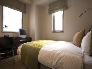 マッサージチェアとセミダブルベッドを備えた広めのシングルルーム。