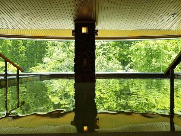 【大浴場】「山月の湯」内湯…湯量豊富な自家源泉かけ流しの湯を、大自然を望む湯舟でご堪能下さいませ。