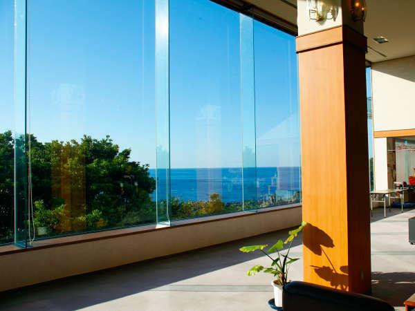 【ロビーからの景色】 大きなガラス張りの向こうに生い茂る『緑』と海の『碧』。明るい陽射しもお出迎え♪