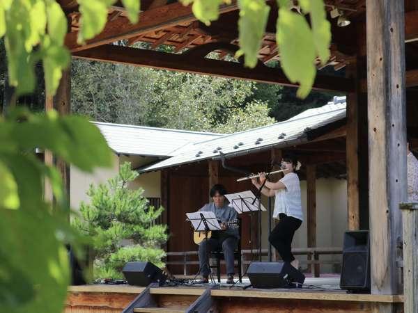 かやぶきの館に併設された能舞台。野外の音楽祭やヨガ体験など様々な催しが開かれます。