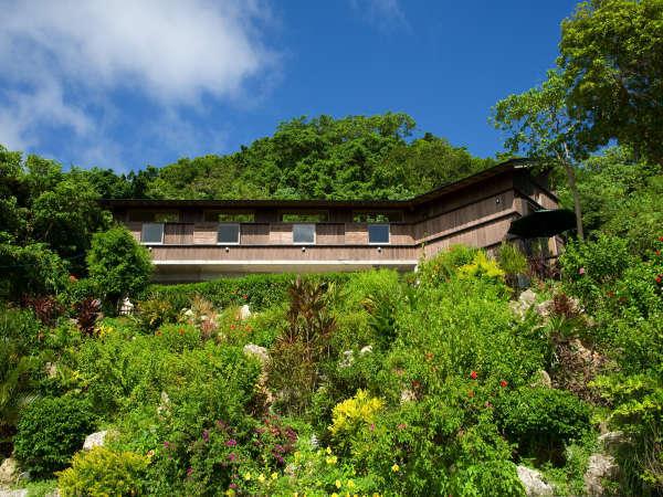 さちばるの海を見下ろす丘の斜面にある、緑の木々や花にひっそりと埋もれる『海が見える小さな宿』です。