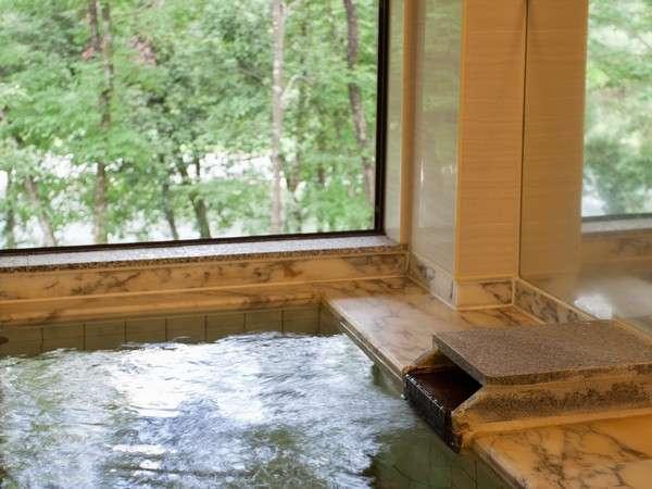 【大浴場】こじんまりとした浴室からは緑の木々の先に清流が望めます。