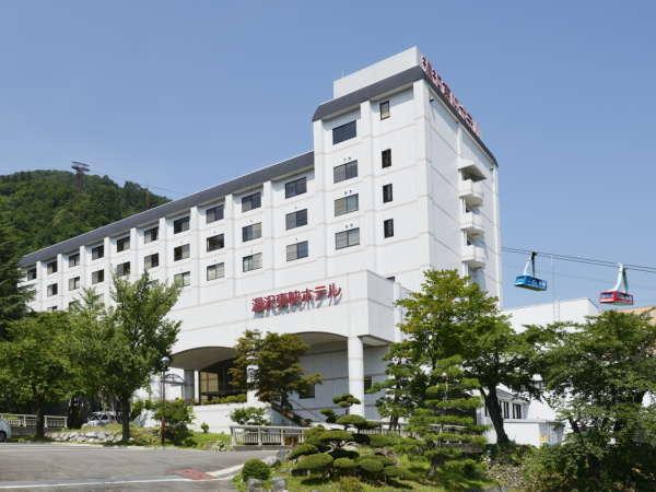 【ホテル外観】 夏の湯沢東映ホテル。エネルギッシュな緑に包まれる。