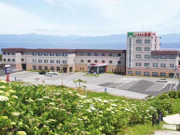初夏のホテル外観。背景に見える山並みは北海道です。