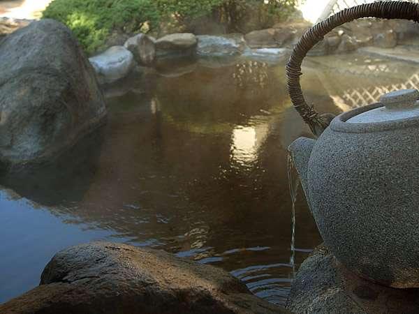 [巨大な石の急須から浴槽へとお茶エキスたっぷりのお湯が注がれています。