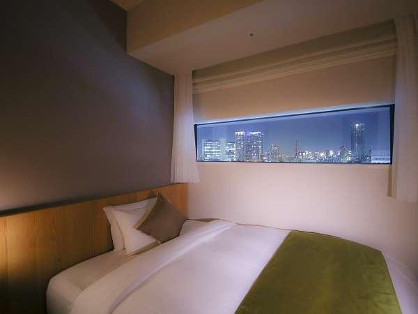 【シングルルーム一例】映画のフィルムをイメージした長方形の窓から見る夜景