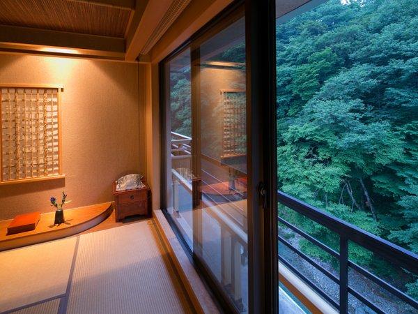 大きな窓から四万川を眺める露天風呂付き客室