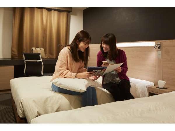 モデレートツインは女子旅にオススメの20平米 ベッドに腰掛けて観光プランを考えてみてはいかがでしょうか