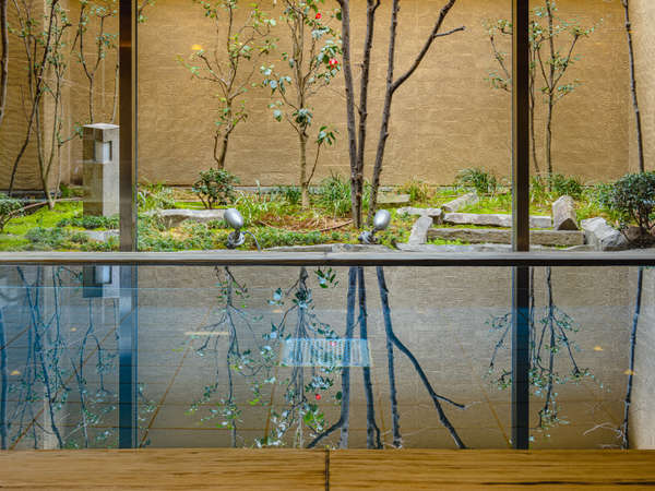 大浴場から窓越しに庭園を眺めながらおくつろぎください。