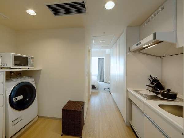 <スタジオ> ドアを開けるとキッチンと、洗濯機。荷物を置かれる充分なスペースも確保できます。