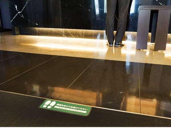 【感染症対策】フロント床にステッカーを貼っています。間隔をあけてお並び下さい。